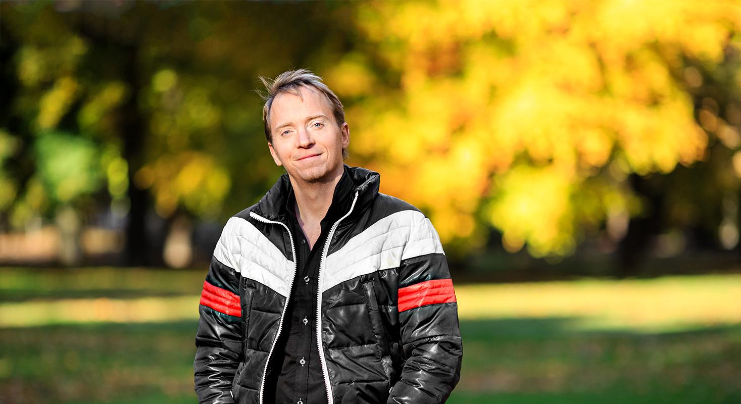 Komikern Håkan Berg i privata kläder ser nöjd ut bland höstlöven