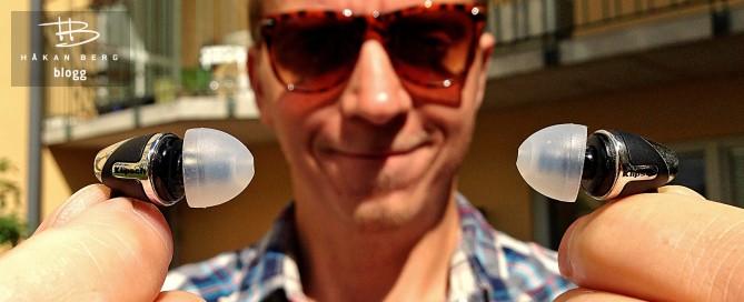 Komikern Håkan Berg håller upp de hörlurar han rekommenderar