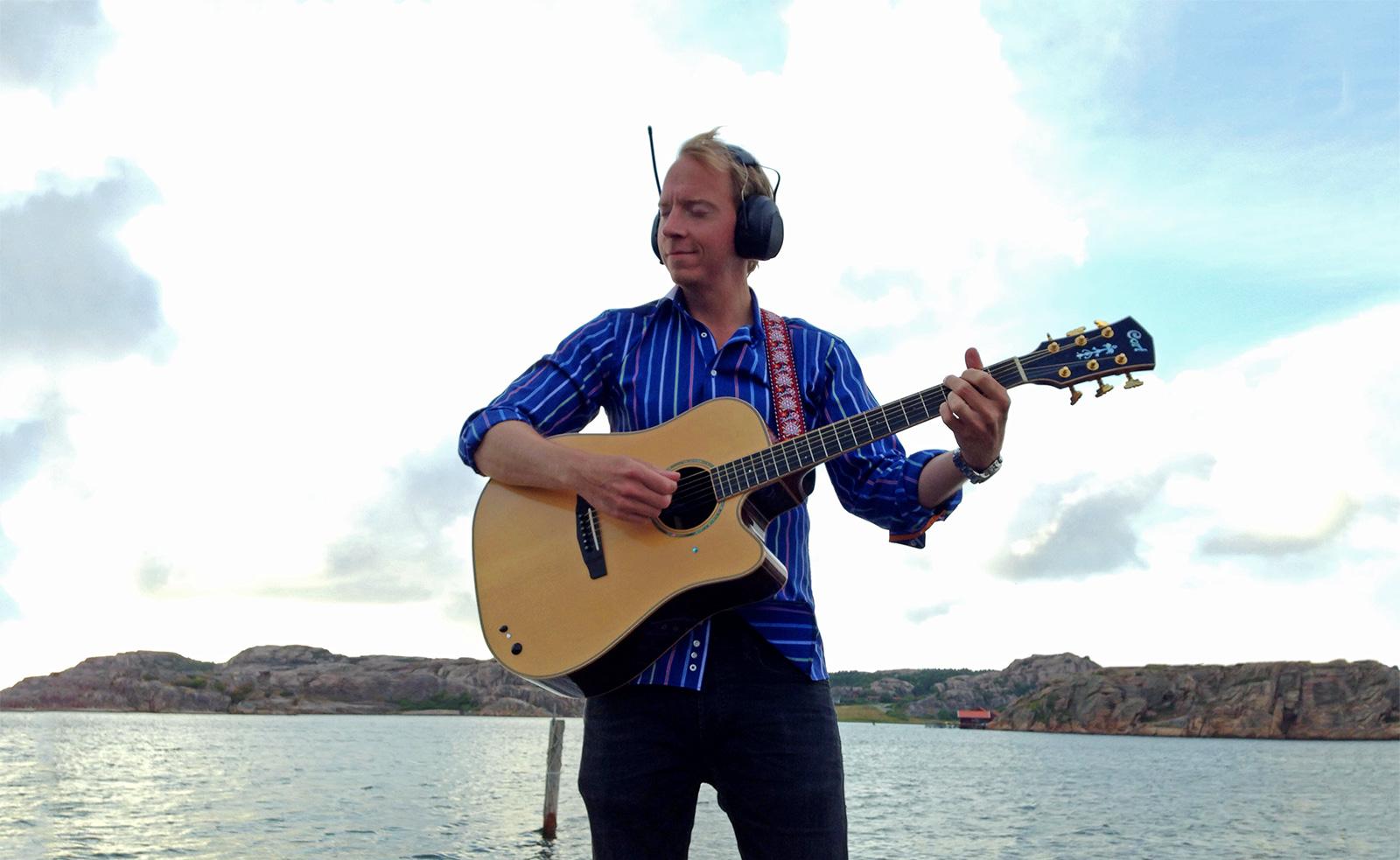 Komikern Håkan Berg spelar gitarr men har på sig hörselskydd med inbyggd radio.