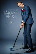 Komikern Håkan Berg håller mikrofon och stativ som en golfklubba