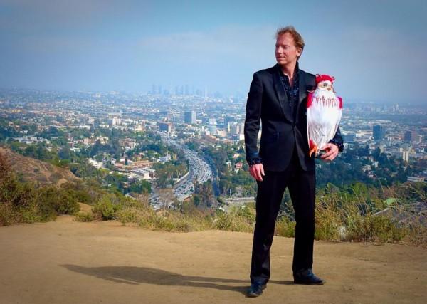 En man med en uggla står i bergen ovanför Hollywood