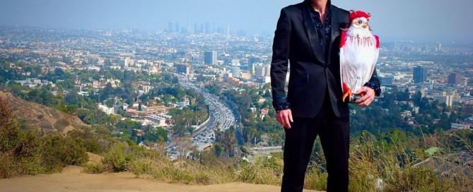 Håkan Berg med uggla står i bergen ovanför Hollywood